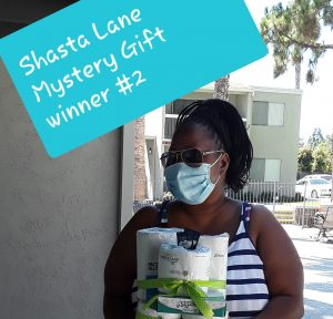 Woman at Shasta Lane shows off the toilet paper she won.